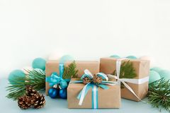 Christmas gift boxes wrapped of craft paper, blue and white ribbons, decorated of fir branches, pine cones and Christmas balls. Royalty Free Stock Image