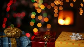 Three christmas gifts in front of fireplace and blurry xmas tree stock footage