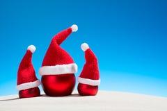 Three Christmas glass balls wearing Santa hats on the beach Stock Photo