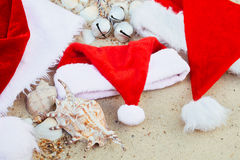 Three christmas hats on the beach. Santa hat  the sand near shells. Family holiday. New year vacation. Copy space. Frame. Top view Royalty Free Stock Photo