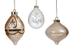 Three christmas ornaments. A trio of gold decorated xmas decorations hanging and isolated against white background royalty free stock images