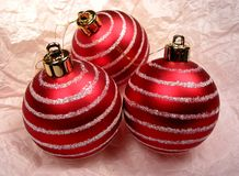 Three Christmas ornaments. Three red Christmas ornaments on the background of pink tissue paper Royalty Free Stock Photos