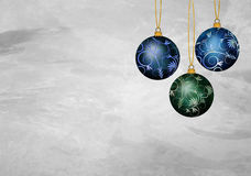 Three christmas ornaments. On a grey textured background with textspace Stock Photo