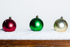 Three Christmas ornaments on a railing Stock Image