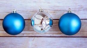 Three Christmas shiny balls on white wooden background Royalty Free Stock Photos