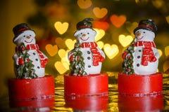 Three Christmas snowmen and heart shaped lights Royalty Free Stock Image