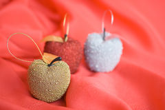 Three christmas tree apples on red background Stock Photos