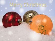 Lying on the snow multicolored Christmas tree decorations. With congratulatory text. Three Christmas-tree colorful balls on the snow with a congratulatory text Stock Image