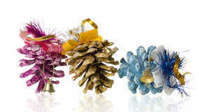 Three Christmas tree cones and bell on white background Royalty Free Stock Photography