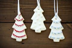 Three Christmas Tree Cookies on Wood Stock Photos