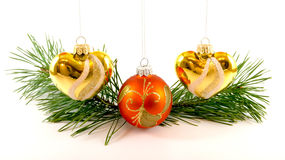 Three Christmas tree toys hanging near spruce branch. Three Christmas tree toys, two heart shaped and one Christmass ball  hanging near spruce branch.  Isolated Stock Photos