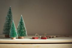 Three Christmas trees on a wooden dresser. Cozy home winter still life. Toned, copy space stock images