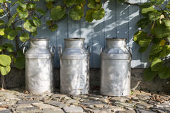 Three churns on a farm Royalty Free Stock Image