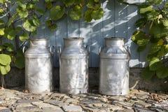Three churns on a farm Royalty Free Stock Image