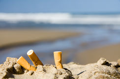 Three cigarettes on beach. Three cigarette butts in the sand on beach with sea in background Royalty Free Stock Photography