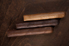 Three cigars. On a dark background Royalty Free Stock Images