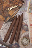 Three cigars and a compass. On the background of old maps Royalty Free Stock Image