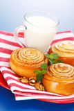 Three cinnamon rolls and jug of milk on red plate Royalty Free Stock Images