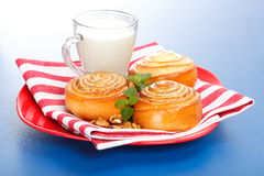 Three cinnamon rolls and jug of milk on red plate Royalty Free Stock Image