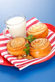 Three cinnamon rolls and jug of milk on red plate Stock Photos
