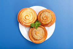 Three cinnamon rolls on white plate Stock Photos