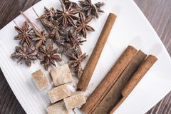 Three cinnamon sticks, anise stars and pieces of brown sugar lie on a white square saucer. On a brown wooden background, top view Royalty Free Stock Photography