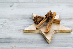 Three cinnamon sticks and anise stars on wooden star. With grey wooden background Stock Image