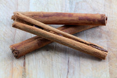 Three cinnamon sticks on a chopping board. A composition with three cinnamon sticks on a wooden chopping board, crossing, portrait cut Royalty Free Stock Photography