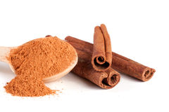 Three cinnamon sticks and powder with spoon isolated on white background Stock Photo