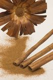 Three cinnamons with brown flower. Powdered cinnamon with pieces of cinnamon and brown flower on the background Royalty Free Stock Photos