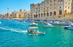 Three cities trip on dghajsa water taxi, Birgu, Malta. SENGLEA, MALTA - JUNE 17, 2018: The dghajsa water taxi floats in marina of Vittoriosa Birgu with medieval Stock Photo
