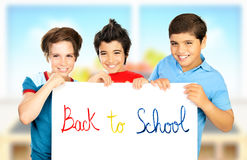 Three classmate boys playing in classroom. Best friends holding white board with phrase back to school, happy pupils having fun at school, smiling children royalty free stock photos