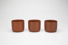 Three clay cups in a row, isolated on white background Stock Photo