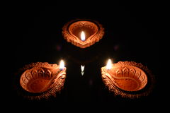 Three Clay Diyas. Three lit clay diyas lamps placed on a black background Royalty Free Stock Images