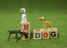 Three clay dogs with alphabet blocks Royalty Free Stock Images