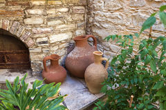 Three Clay Pitchers Standing At The Stone Wall Background. Royalty Free Stock Images