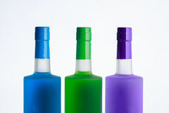 Three clear alcohol bottles with blue, green and purple liquids. With plastic caps on a white background Royalty Free Stock Photo