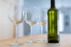 Three clear wine glasses and a bottle of chilled white wine on a Royalty Free Stock Photos