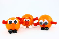 Three Clementines With Funny Faces. Three clementine fruits decorated with assorted candies and plastic eyes to create fun creatures Royalty Free Stock Photo