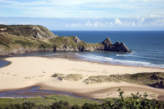 Three Cliffs Bay, Wales. Three Cliffs Bay on the Gower Peninsular, West Glamorgan, Wales, UK, which is a popular Welsh coastline attraction of outstanding beauty stock images