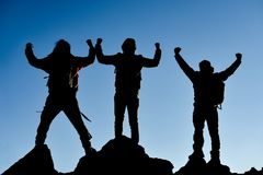 Three climbers on mountain peak. Team of three successful climbers celebrating upon reaching the  mountain summit  seen in silhouette against a pale blue sky Royalty Free Stock Image