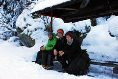 Three climbers resting on a bench in Retezat mountains, Romania Stock Photos