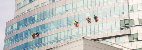 Three climbers wash windows and glass facade of the skyscraper Stock Images