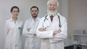 Three clinicians in white coats looking and smiling at camera. stock video footage
