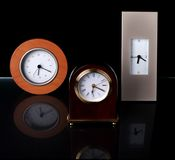 Three Clocks. Stacked on each other against a black background Royalty Free Stock Photography
