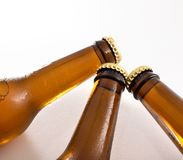 Three closed beer bottle necks on white table with fresh water drops. Top view stock images