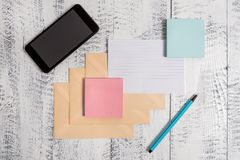 Three closed rectangular colored envelope ruled paper sheet smartphone sticky note pads marker lying wooden retro. Envelopes marker ruled paper smartphone sheet stock photography