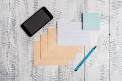 Three closed rectangular colored envelope ruled paper sheet smartphone sticky notes pad marker lying wooden retro stock image
