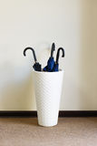 Three closed umbrellas in basket. Royalty Free Stock Photography