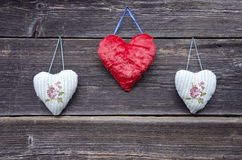 Three cloth heart symbols on old wooden wall Stock Images
